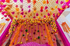 Mehendi Decor - Manav & Sareena wedding story | WedMeGood | Pink and Orange Wedding Decor with Hanging Pom-poms #wedmegood #indianbride #indianwedding #mehendidecor #hangingdecor #mehendi #DIYdecor #marigold