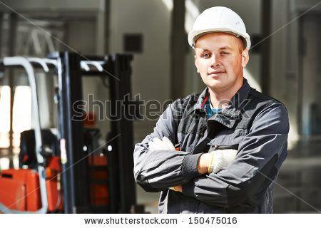 young smiling warehouse worker driver in uniform in front of forklift stacker loader by Dmitry Kalinovsky, via Shutterstock