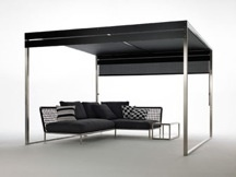 Pergola XG1 sunshade in satin-finish stainless steel, polyurethane, and plasticized mesh, with Nest sofa and side table in stainless steel by Coro Italia, through Lepere is perfect for any outdoor area and so much fun for Summer!