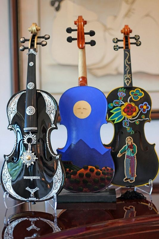 """Left to right: Lawrence Baca, """"The Silver Violin 'Apres un Reve;'"""" David Bradley, """"Song of the Wind;"""" Terri Greeves and Dennis Esquivel, """"Ode to the Metis Fiddlers"""" For a fund-raiser for the Santa Fe Symphony, over 50 artists were asked to decorate, transform, or otherwise mess about with a violin to produce a unique work of art."""