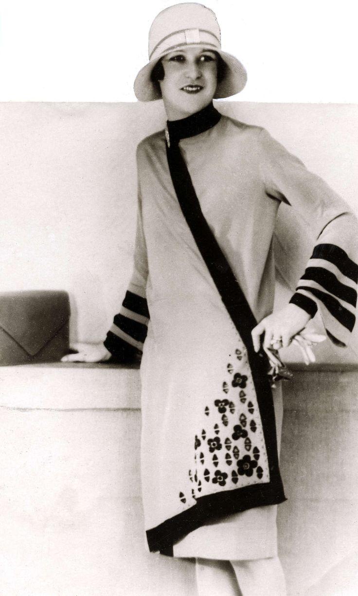 Damesmode. Schuin gesneden jas met donkere bies aan de hals, op de mouwen en aan de voorzijde. Dit jasje behoort tot de najaarscollectie van 1927. Zonder plaats, 1927.