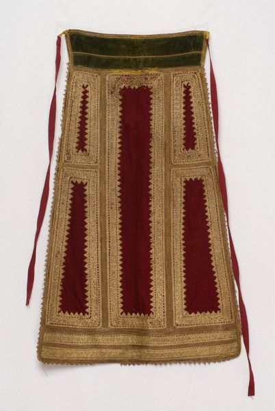 Sarakatsana chrysi, the Karagouni gold embroidered bridal apron made of crimson felt. This type of apron is worn in the region of Thessaly (Θεσσαλία), from Karditsa (Καρδίτσα) in the west to the villages of Palamas (Παλαμάς) and Sofades (Σοφάδες) in the east © Lyceum Club of Greek Women