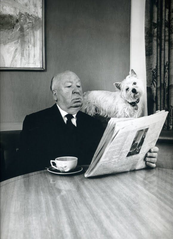 Alfred Hitchcock and friend, reading the newspaper together.