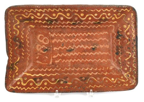 """Pennsylvania redware loaf dish, dated 1788, with yellow slip wavy line decoration, 11"""" h., 16 1/2"""" w.   sold   3318.00"""