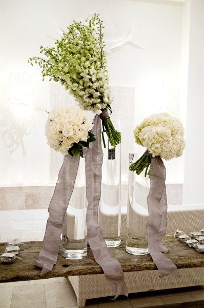 "More ""bunches"" (or bouquets) placed  at a tilt in large cylindrical vases. Modern floral decor at it's prettiest ;)"