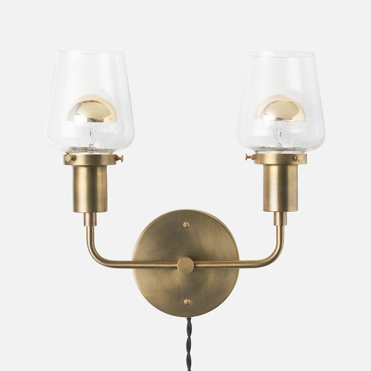 A modern palette for personalization, the delight of the Abrams Double Sconce is in the details. Featuring custom, streamlined fitters crafted for Schoolhouse, this solid brass double sconce can be dressed up with a wide range of bulbs and shades, offering an opportunity to update according to mood or season.