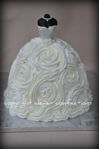 "Wedding Gown Cake By cambo on CakeCentral.com Gown is 9"", 8"", 8"", 6"" cakes, stacked and carved slightly; crumb-coated and then covered with buttercream rosettes using 1M tip. Bodice is fondant over barbie doll body (no legs inside cake); embellished with edible sugar glitter, silver dragees and sugar pearls"