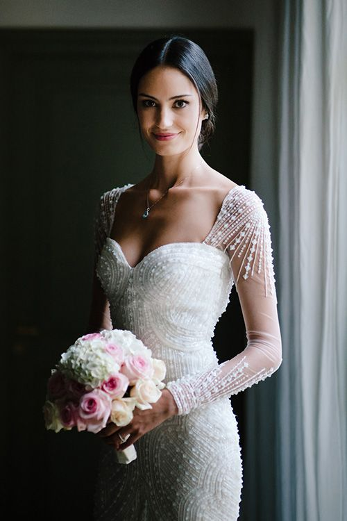 A gorgeous long-sleeved @pronovias wedding dress with sequins and beading| @nicolaschauveau | Brides.com. The sleeves are so unique, I really like that.