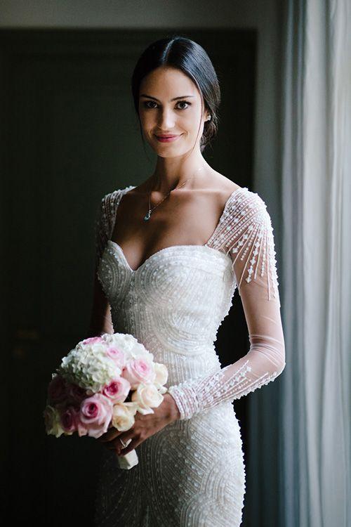 A gorgeous long-sleeved @pronovias wedding dress with sequins and beading| @nicolaschauveau | Brides.com