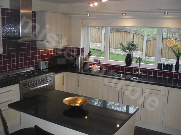 Absolute Black granite worktop, gloss white cupboards and red tiles