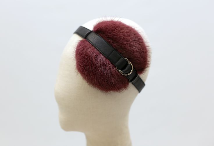 A cocktail hat made of recycled fur and a leather strap and metal detail.  #millinery #cocktail #fur #sustainable #leather #Burgundy #hat #headpiece