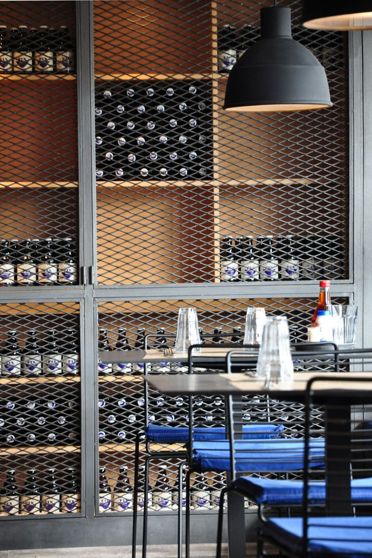 Large caged cupboards used for storage in this cafe giving the space an industrial style. The look is further achieved with the repetition of bottles creating clean lines and a sense of order.