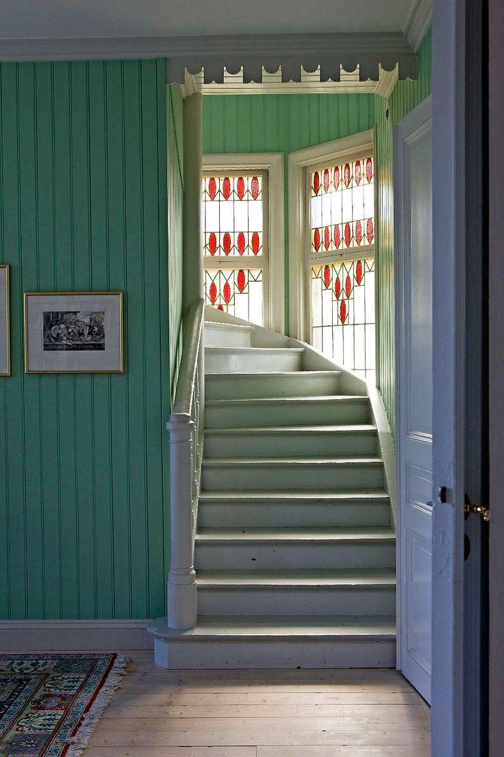 Kulören i hallen hittade Eva bakom ett element och målade om pärlsponten i den. Trappans blyinfattade glasfönster är typiska för nationalromantiken.