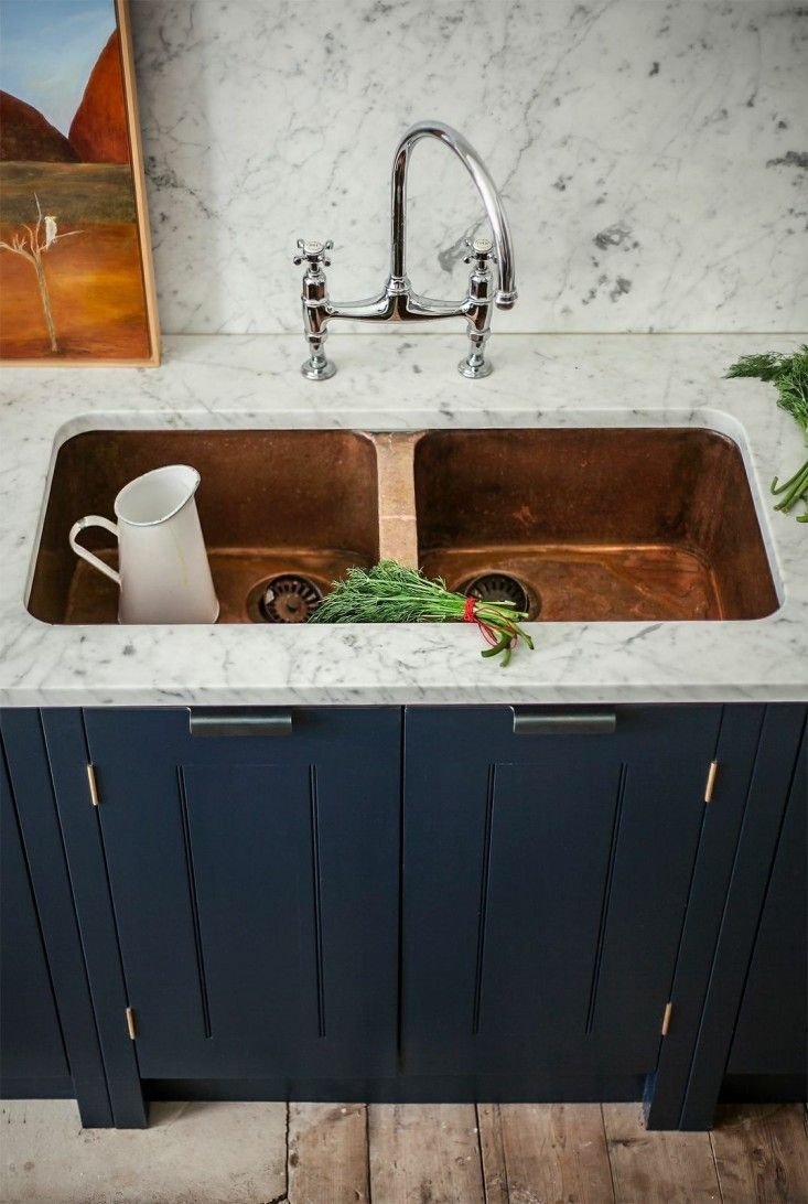 kitchen renovation inspiration - under mounted copper sink with marble countertops and navy blue cabinets