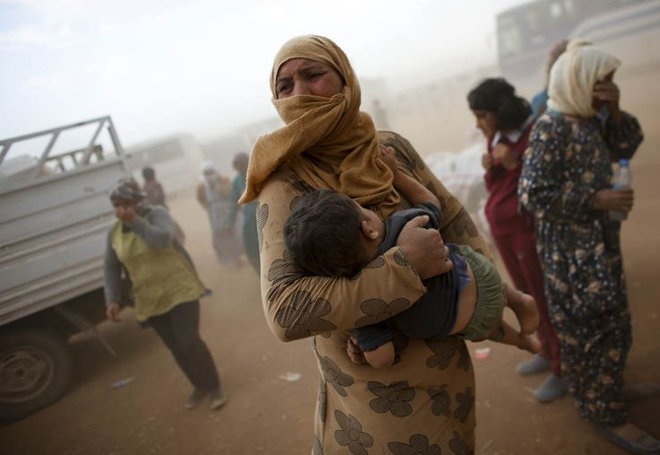 A Kurdish Syrian refugee waits for transport during a sand storm on the Turkish-Syrian border near the southeastern town of Suruc in Sanliurfa province, September 24, 2014. The United Nations refugee agency said on Tuesday it was making contingency plans in case all 400,000 inhabitants of the Syrian Kurdish town of Kobani fled into Turkey to escape advancing Islamic State militants. (REUTERS/Murad Sezer)