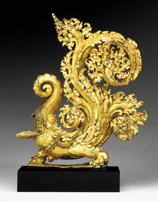 A Gilt Bronze Makara Finial Tibet, 13th/14th Century The mythical creature with crocodile body elaborately cast with gaping mouth and coiled trunk, its tail rising up in a finely detailed foliate swirl, thickly cast from high copper content bronze with rich gilding, the base plate with two prongs.