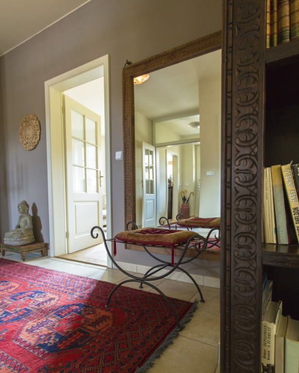 Entrance hall in the modern interior accesorized with antique afghanistan carpet and old indian library.