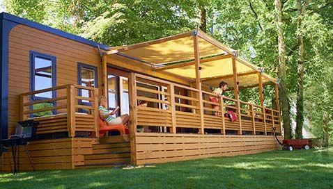 Eurocamp Luxus-Mobilheim Aspect: Geräumiger Wohnbereich, moderne Küche, und eine besonders große, überdachte Holzterrasse mit bequemen Terrassenmöbeln für einen perfekten Campingurlaub.