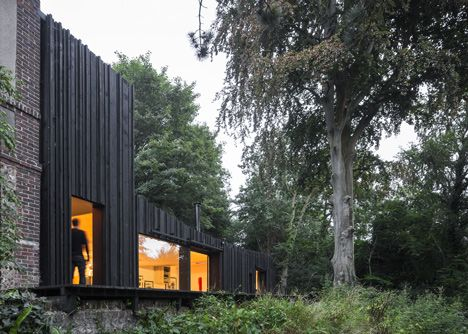 Blackened timber house extension with textured walls by Marchi Architectes