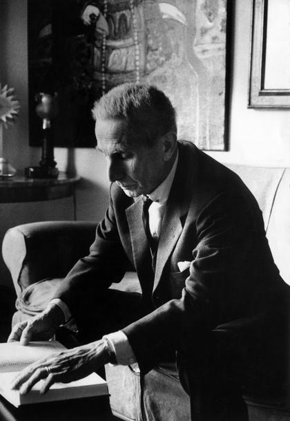 Milano, 1971. Dino Buzzati, scrittore, giornalista e pittore italiano, legge seduto sul divano nella sua abitazione.