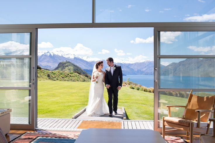 A gorgeous bride and groom walking into Whare Kea Lodge after their wedding ceremony on the lawn overlooking Lake Wanaka and the Southern Alps.  Photo by Alpine Images Co Ltd.