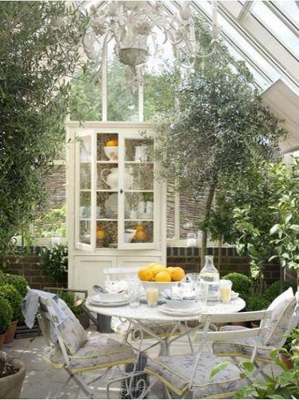 Fancy antique metal garden table and chairs mixed with an old white cupboard fill this greenhouse room.