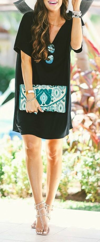 Black shift dress with a pop of color and pattern in a clutch bag