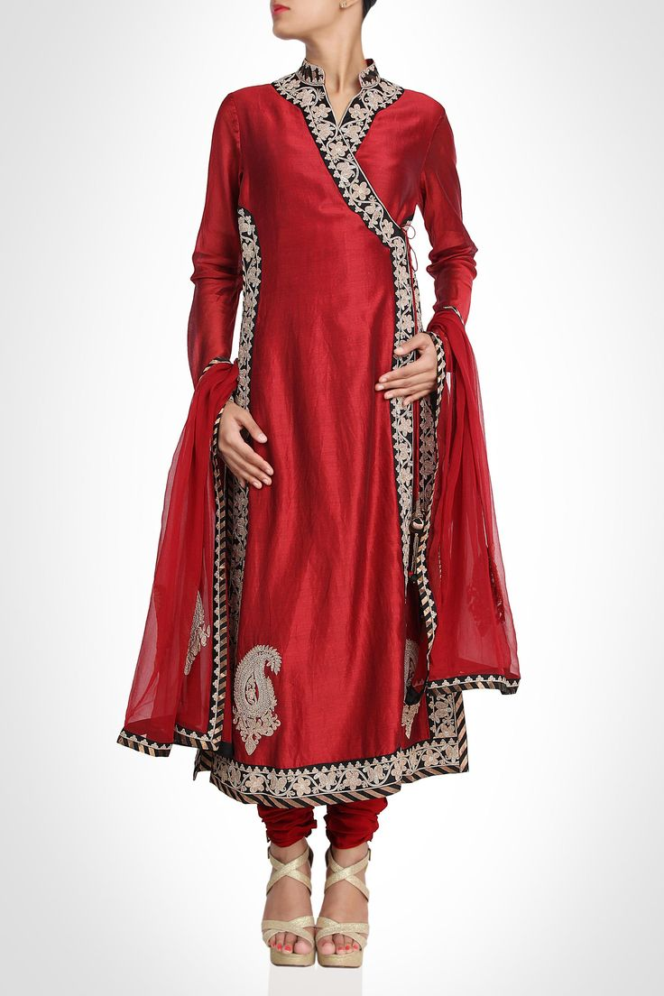 Embrace the traditional style with this angrakha style red suit lined with zari border. Lending a luxurious appeal to the outfit is the zari bordered hem and ornate zardosi work on the brocade sleeves