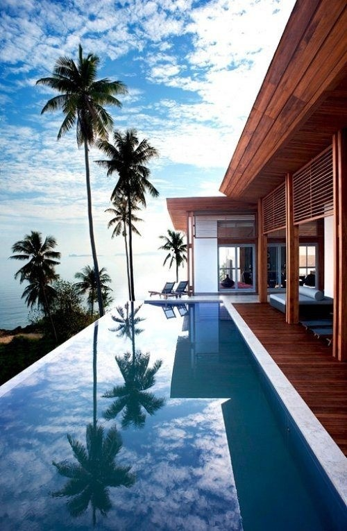 log cabin house on beach front property with an infinity pool