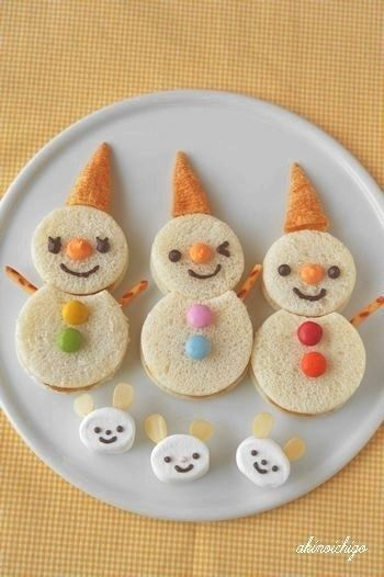 Cut sandwiches into snowmen and top with Bugles. | 41 Adorable Food Decorating Ideas For The Holidays