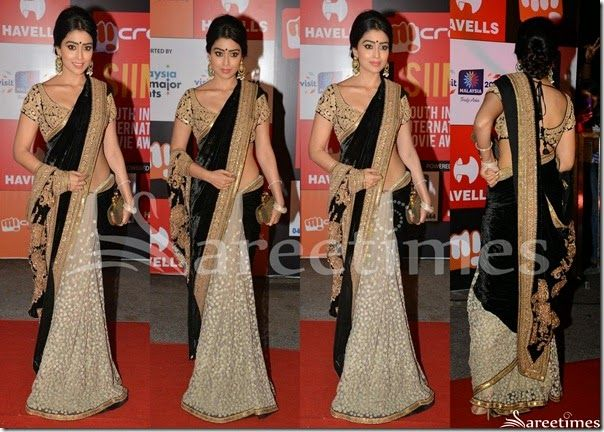 Bollywood and South Indian actress Shriya in beautiful black and white half and half saree. Designed by Sabyasachi at SIIMA 2014. White embellished patch work designs all over white saree. Gold embellished  crystalized glittering work across it border. Paired with designer short sleeves saree blouse for back. Gold applique patch work designs all over blouse.