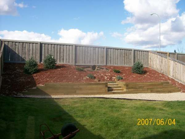 This steep slope is retained with an anchored wall using landscaping timbers. Fabric was applied to the hill and decorative rocks and shrubs were planted. The stairs add interest and allow access to the shrubs. Picture compliments of Dream-yard.