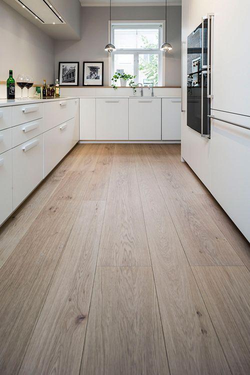 Trägolv, vita skåp, ljustgrå väggar och träbänkskiva