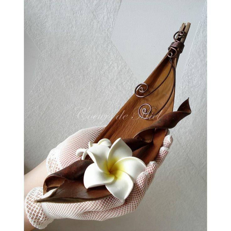 Le porte alliance YANA pour une décoration mariage exotique. DESCRIPTION : Naturel et fleuri, ce porte alliance sera idéal pour un mariage au thème sur les îles exotiques. Réalisé à partir d'une coque de Maripa (barque coco), ce coussin d'alliance est orné de fleurs de frangipanier. Vous pourrez y maintenir vos alliances grâce aux arabesques.
