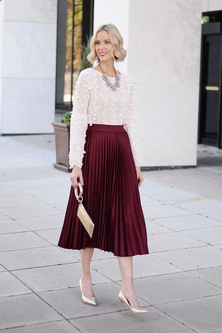 burgundy pleated midi skirt, white textured floral blouse, gold heels, statement necklace, holiday outfit idea