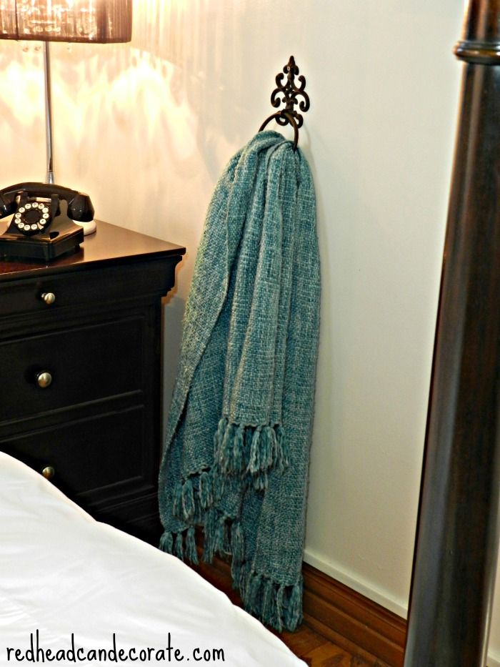 Who says towel rings are just for towels? We use this one for our throw, or for our clothes.  No molly required, just find your stud, and screw it in somewhere close to your bed.