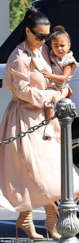 Holding her close: Kim carried the two-year-old as they headed to the local cinema