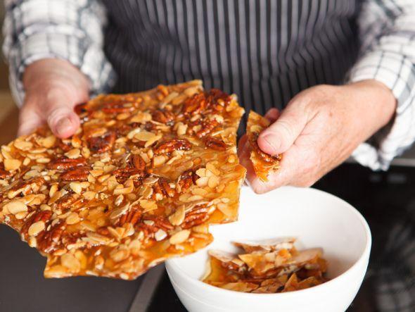 Karamell mit Nüssen wird in Stücke gebrochen