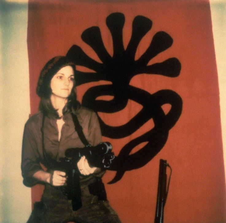 """Patricia """"Patty"""" Hearst Wearing Combat Fatigues and Holding a Sawed-Off M1 Carbine at the Ready Is Photographed Standing in Front of The Symbionese Liberation Army Seven-Headed Naga Emblem in April 1974. The Symbionese Liberation Army (SLA) Was An American Self-Styled Left-Wing Revolutionary Organization Active Between 1973 and 1975 That Considered Itself A Vanguard Army. The Group Committed Bank Robberies and Other Acts of Violence Resulting In Two Murders."""