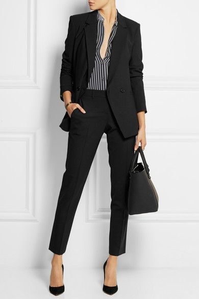 Black suit with a black and white striped or patterned blouse, watch, black heels, and black purse. Any jewelry worn should be black, white, or silver. Monochrome look.
