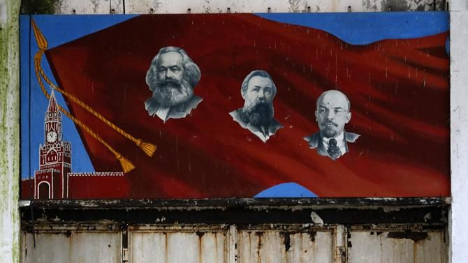 In this photo taken Friday, Nov. 7, 2014 a mural depicting Communist leaders, from left, Karl Marx, Friedrich Engels and Vladimir Lenin hangs on a wall of a bomb assembly and repair facility in an abandoned ex-Soviet military base near Nagyvazsony, Hungary. Abandoned by the Soviets in March 1990, a few months after the fall of the Berlin Wall and just weeks before Hungary's first post-communist elections, the base looks like a set for a post-Apocalyptic film. (AP Photo/Darko Vojinovic)