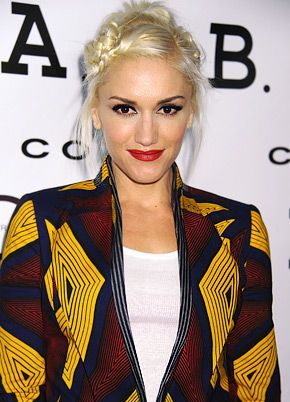 Gwen Stefani - Amazing African-style patterned jacket, in blue, yellow and brownish-red. Hair plaited and rolled up to side.