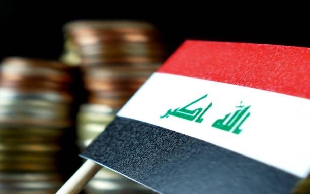iraq flag waving with stack of money coins macro