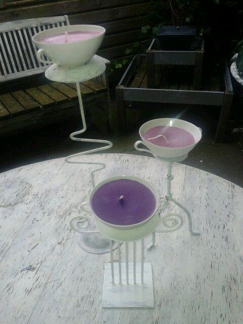 Kopjes op standaards met zelfgemaakte kaarsen.