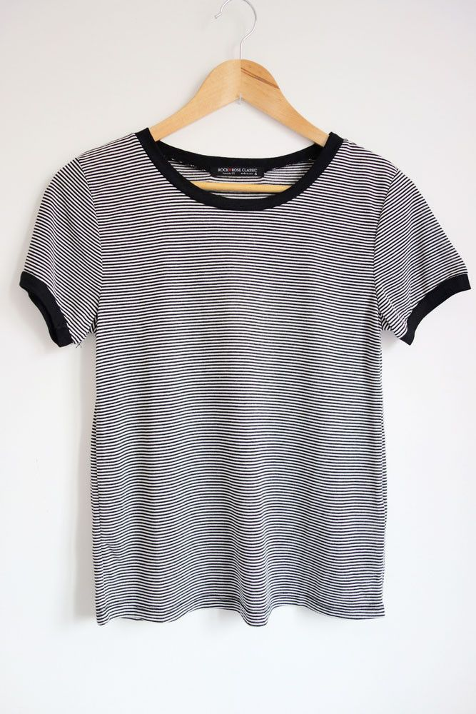 Super soft, semi-fitted t-shirt features thin black and white stripes all over and black contrast trim along the neckline and short sleeves. Tee is stretchy and is cute styled with jeans and a flannel