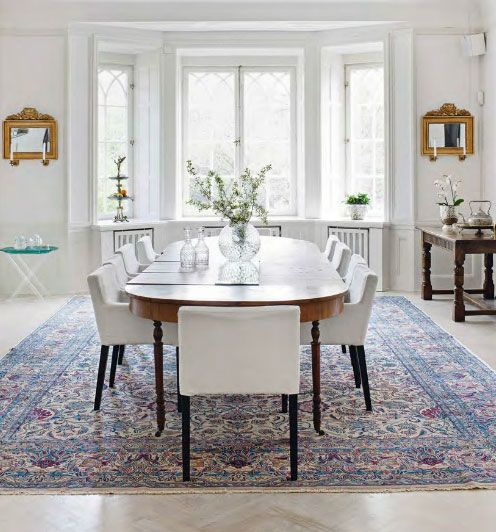 """A carefully edited selection of Modern artworks forms the perfect counterpoint for the heirloom antiques that furnish this family home. The biggest room in the apartment is used as a dining room with an antique fold out dining chair that can seat up to 30 people, chairs are """"Nils Chairs"""" from Ikea. Stunning sitting room…"""