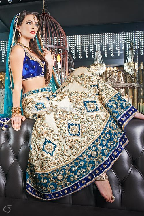 Bridal Lenghas - Contemporary wedding outfit with a royal blue velvet blouse and champagne gold skirt with a double border of teal and blue