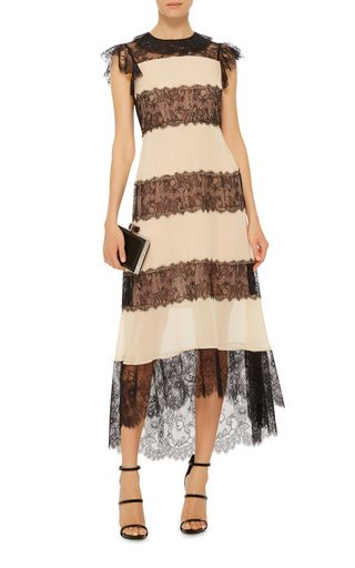 This **Philosophy di Lorenzo Serafini** dress is rendered in a silk georgette and features a sheer lace yoke with ruffled cap sleeves, panels of lace layered throughout, and a floor length skirt with a scalloped hem.