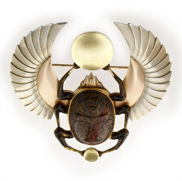 European Egyptian - Revival Art Deco hardstone and tri-coloured gold beetle brooch, the brooch in the form of a winged scarab beetle, symbolising the rising sun, with oval carved hardstone body and three pairs of legs, the front and back legs clasping circular yellow gold plaques of differing sizes, the outspread wings of rose and white gold, all in 14 carat gold with brooch fitting, all measuring approximately 7.5x7.5cm, gross weight 53.5 grams, circa 1925.