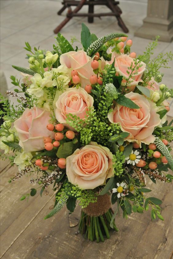 Romantic and elegant.. Soft peaches and pale yellow.. roses, hypericum berries, stock , veronica and more.